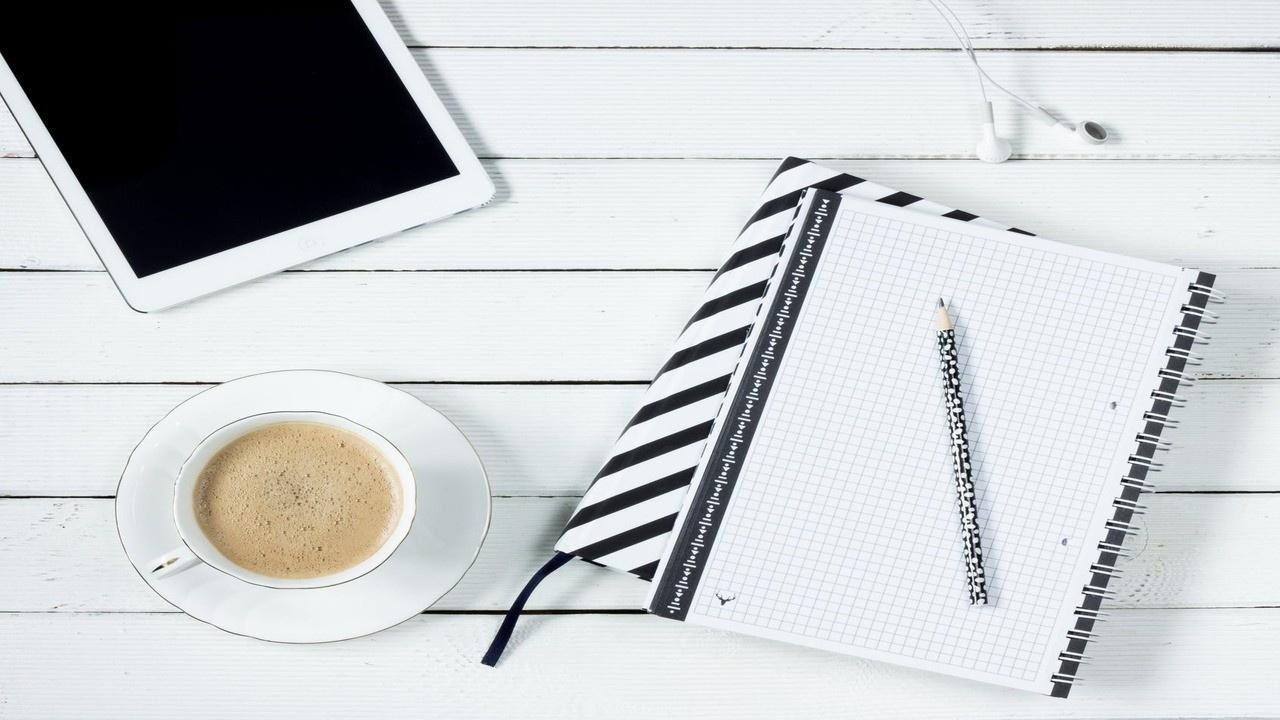 una mesa con un cafe, anotador y una tablet