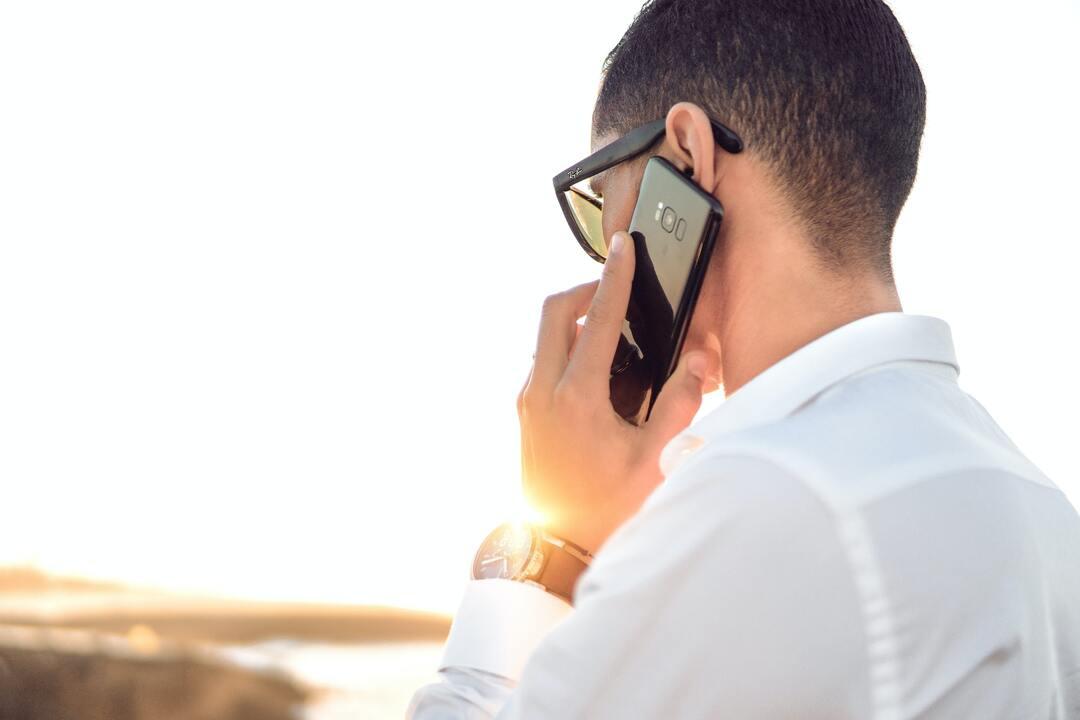 Hombre hablando por teléfono frente a un atardecer