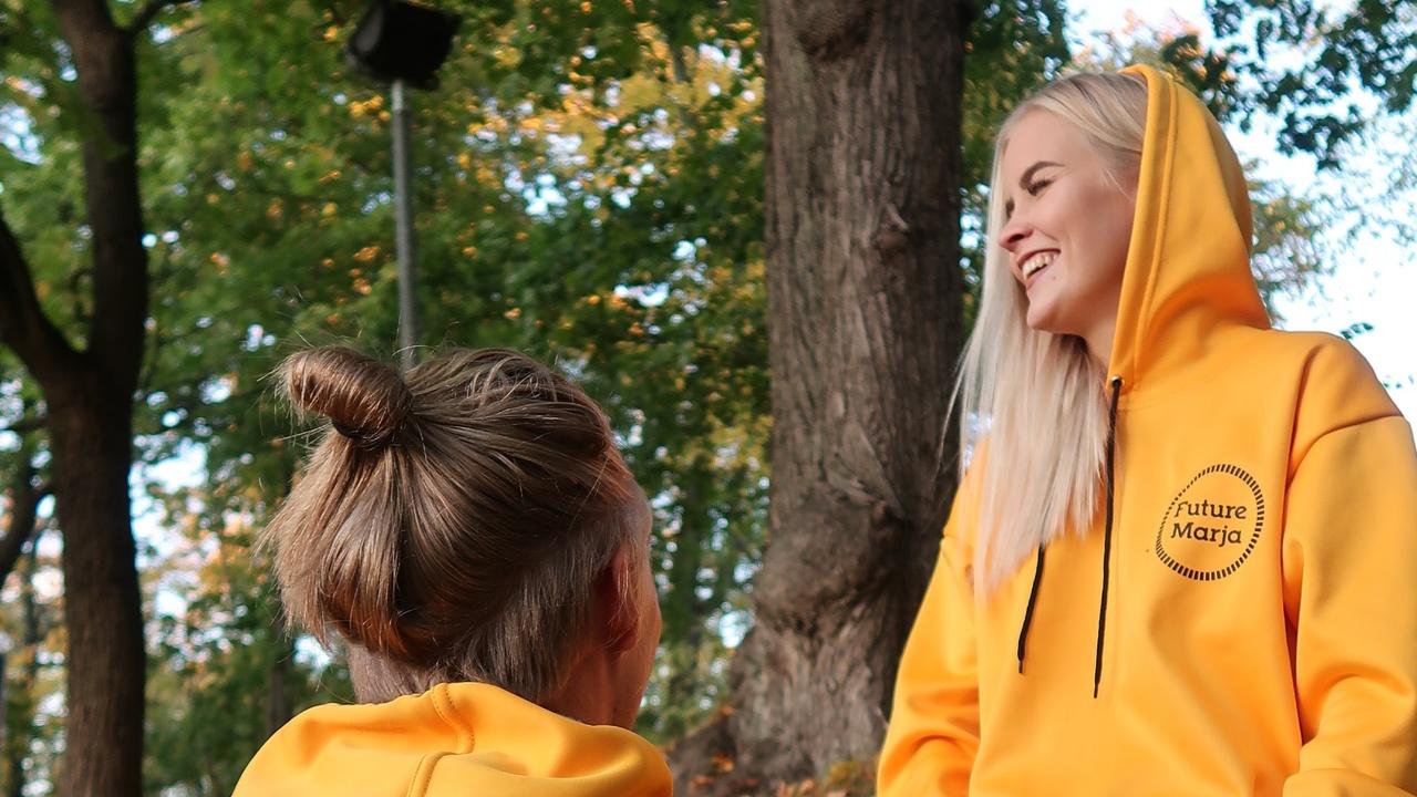 mies ja nainen puistossa keltaisissa huppareissa. Hupparissa logo FutureMarja.