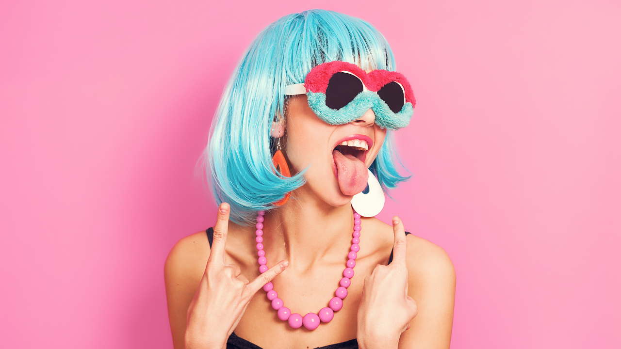 Woman with blue hair, funky glasses and a rebel misfit attitude owning her uniqueness instead of conforming or fitting in
