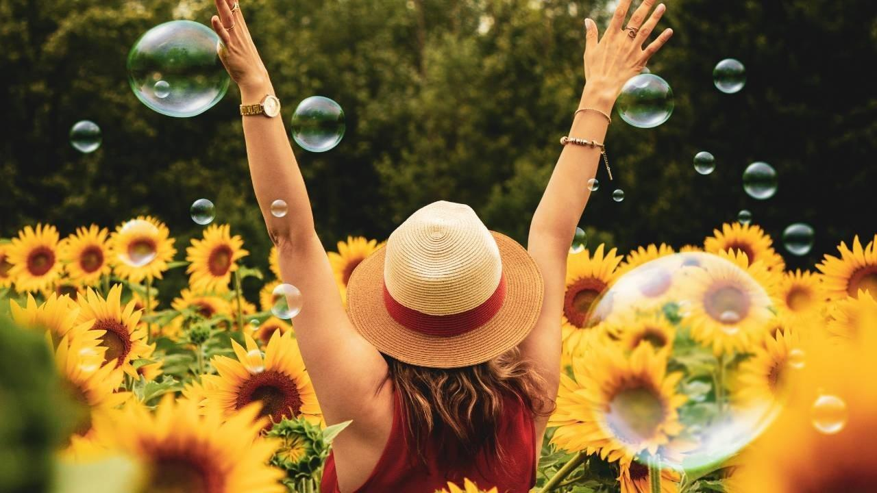 Be Bold and Fearless In The Pursuit Of Your Own Happiness - woman in a field of sunflowers with bubbles to represent freedom and happiness