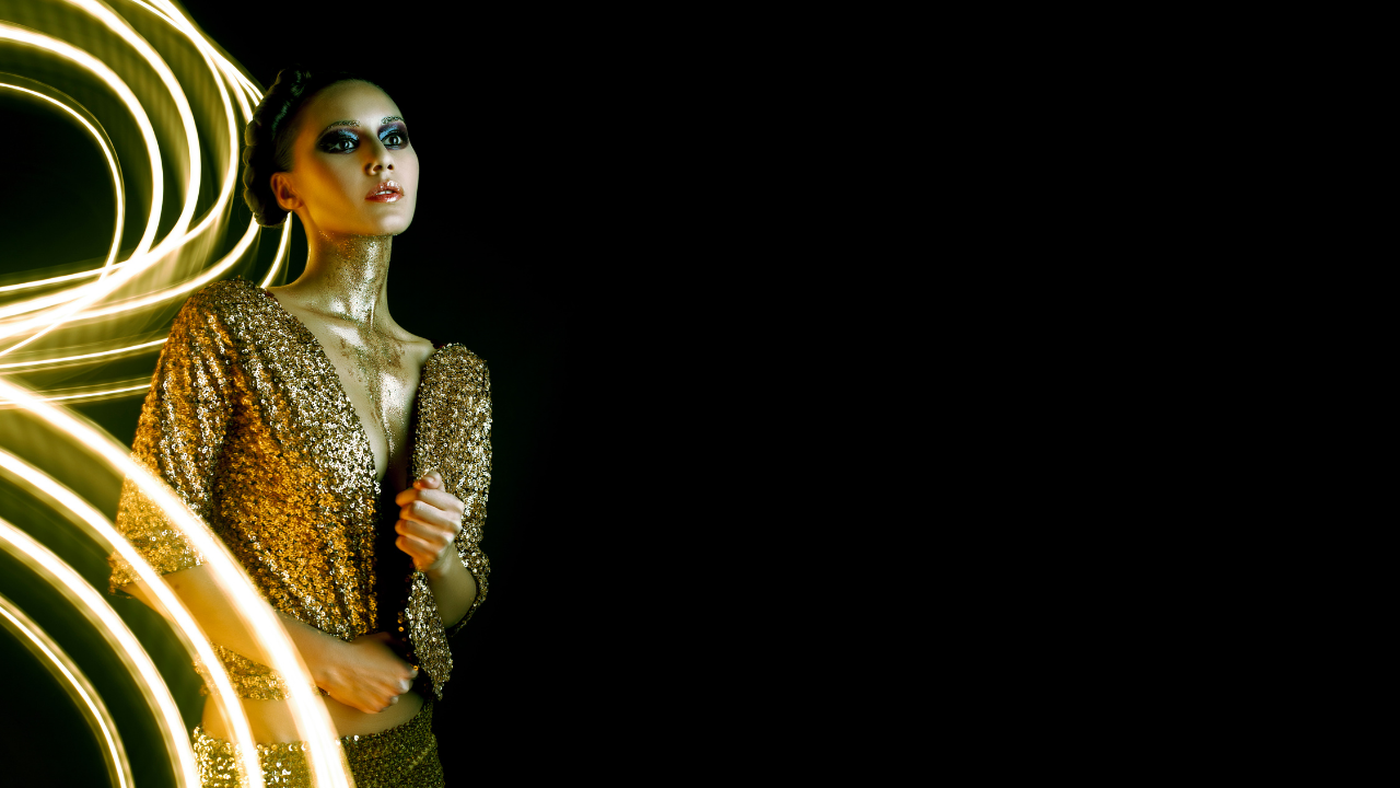 woman dressed in gold known as a cosmic girl with a black background with the contracting black and gold to represent the gold within the shadow