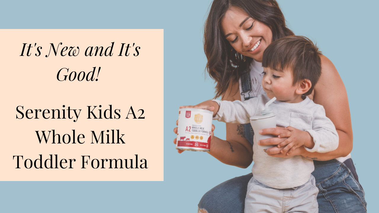Toddler holding a grey straw cup in mother's arms touches a can of Serenity Kids A2 Whole Milk Toddler Formula while smiling