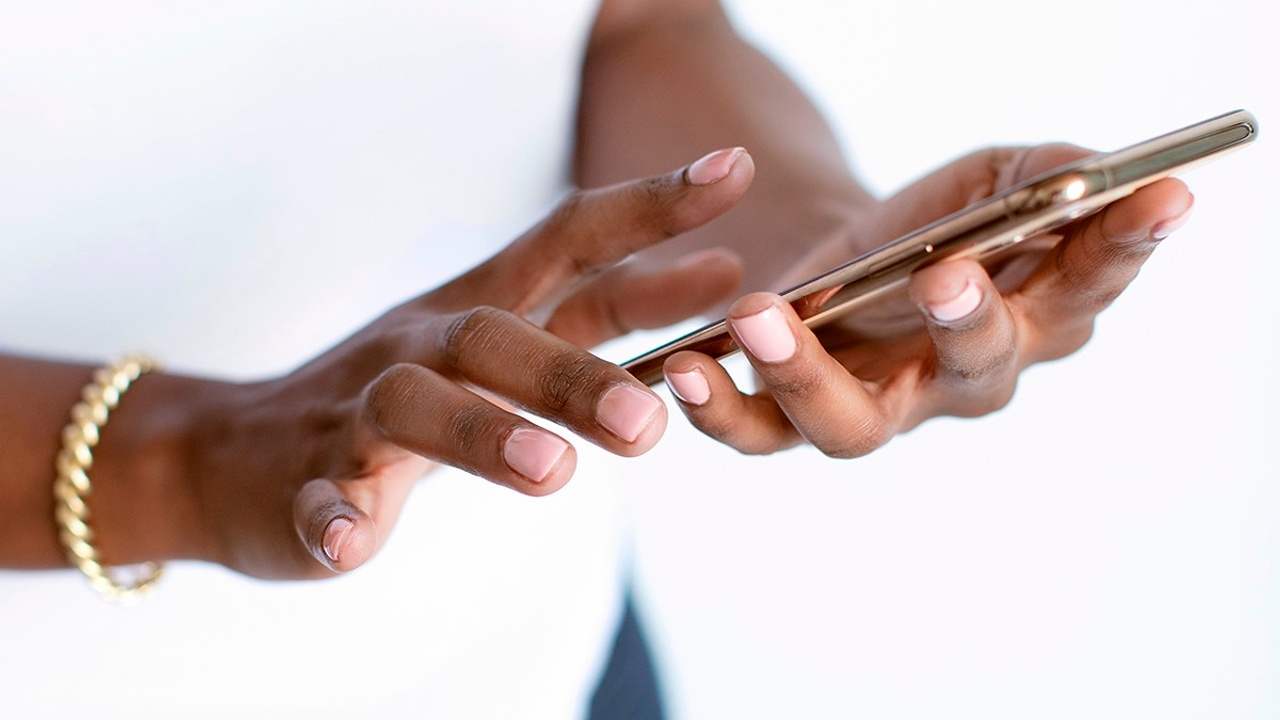 Close-up shot of Black woman in white shirt with gold jewelry holding an iPhone