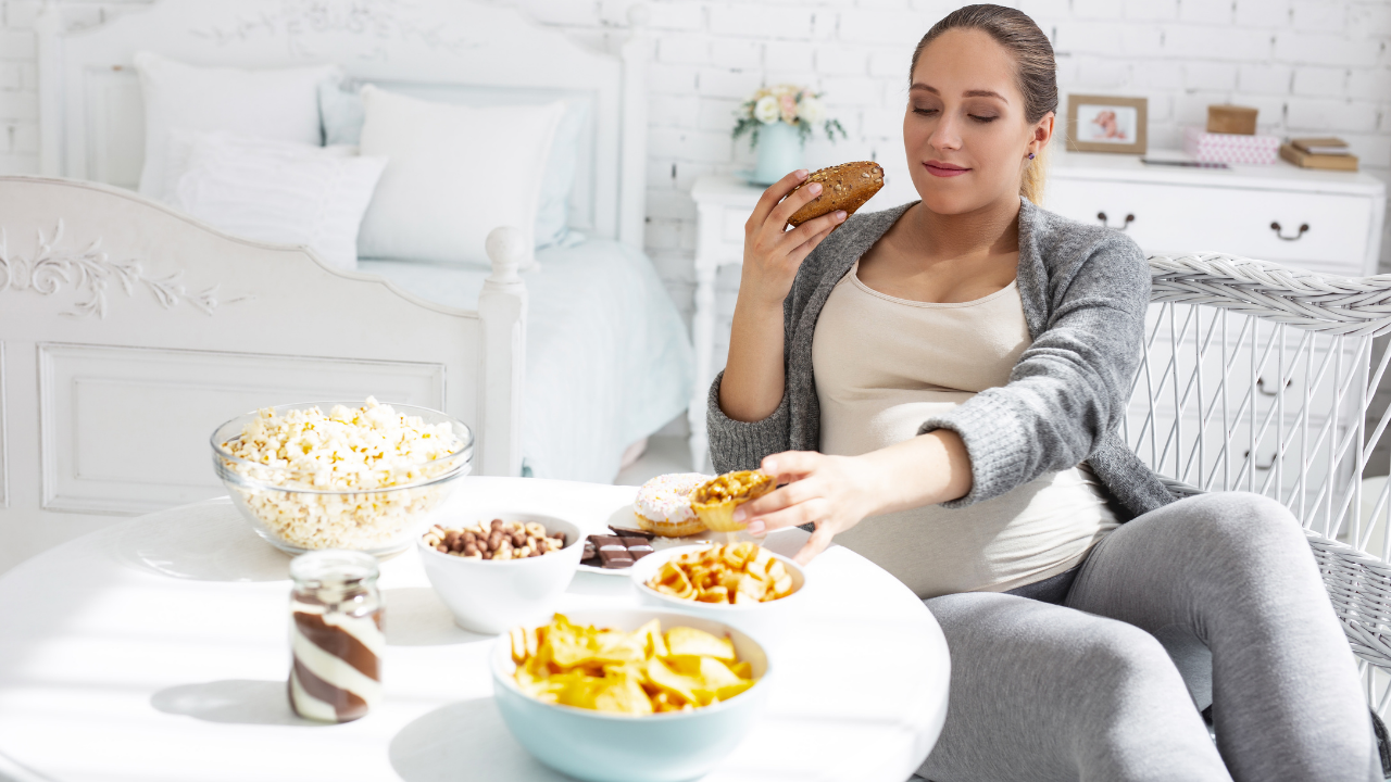 Pregnant woman surrounded by snacks.