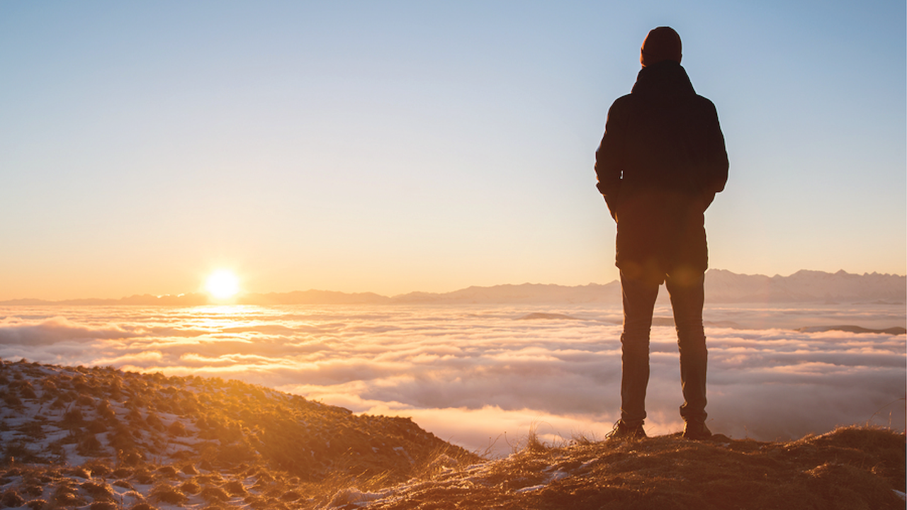 The back of a man high in the mountains looking at the setting sun in a valley filled with clouds.