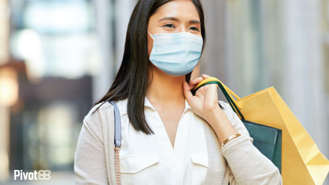 Young woman wearing protective medical mask holding shopping bags in city