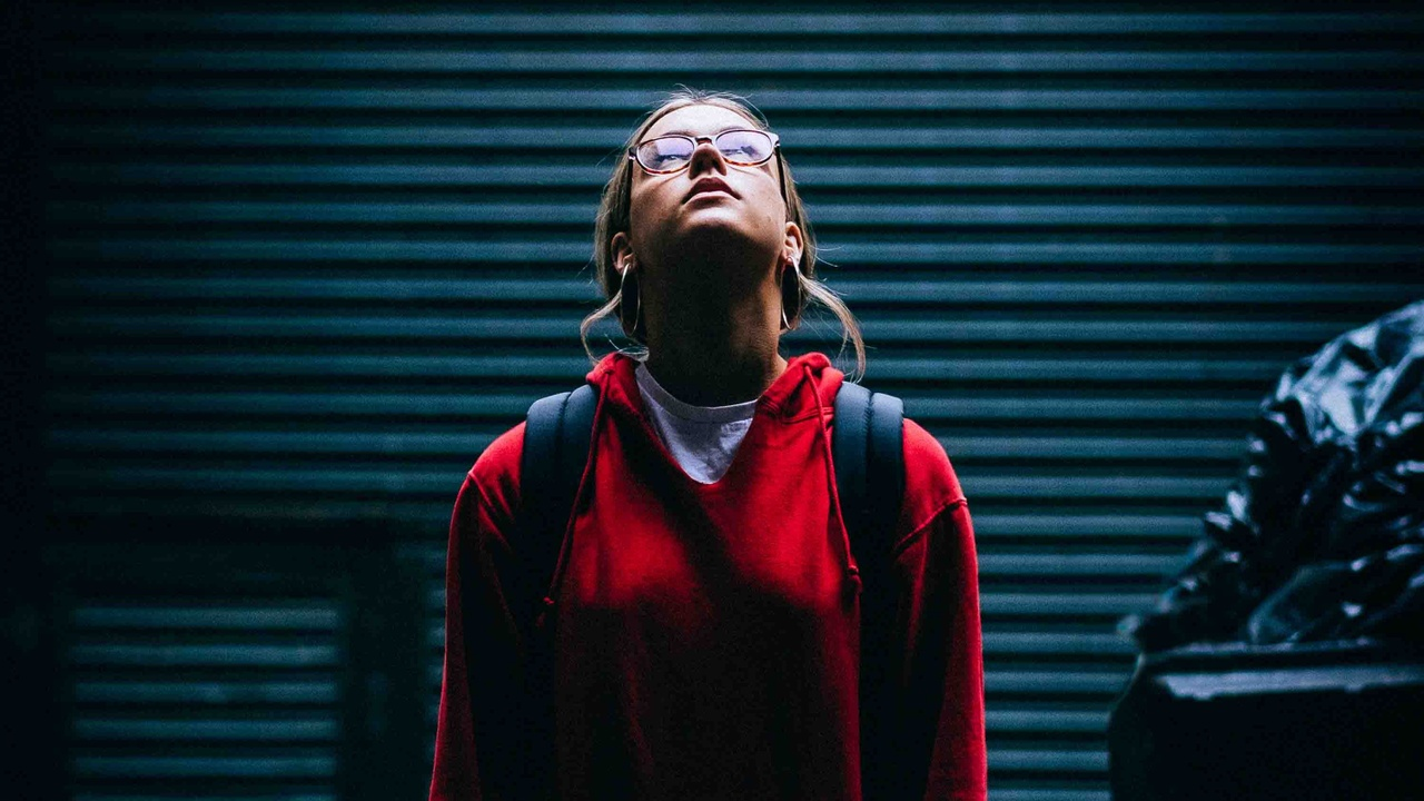 Woman in red hoodie looking up. Representing an INTP Personality.
