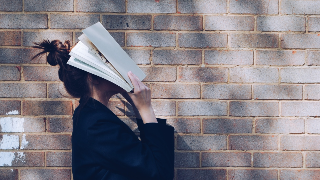 A woman holding a book in front of her face next to a brick wall.