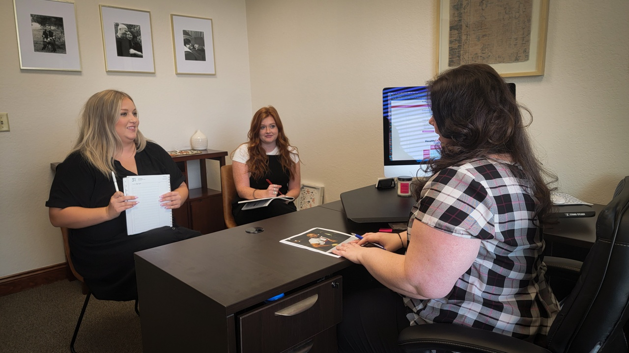 Healthcare Express's Chief Branding Officer, Lauren Butler, having a meeting with two of her team members, Lexie and Brooke.