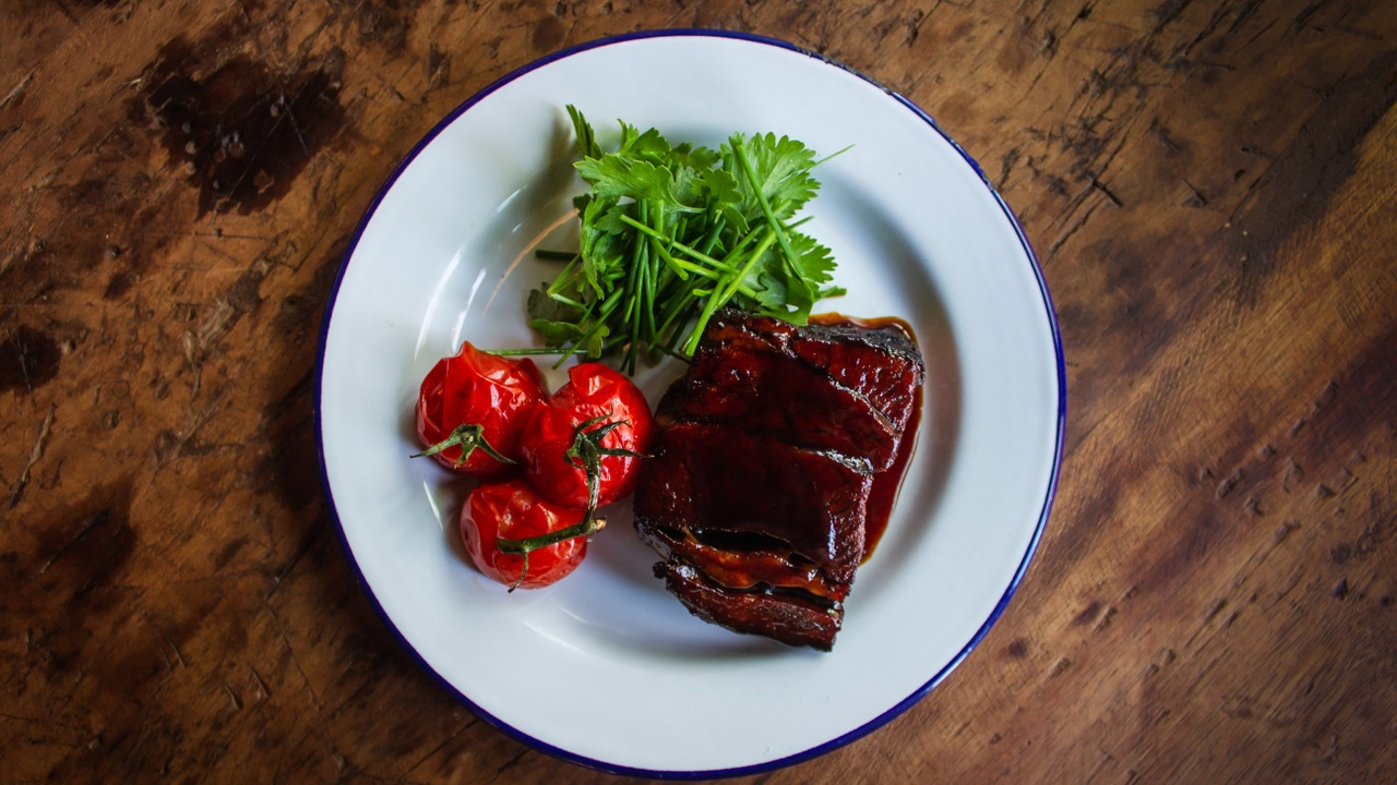 white plate with meat red tomatoes and green herbs