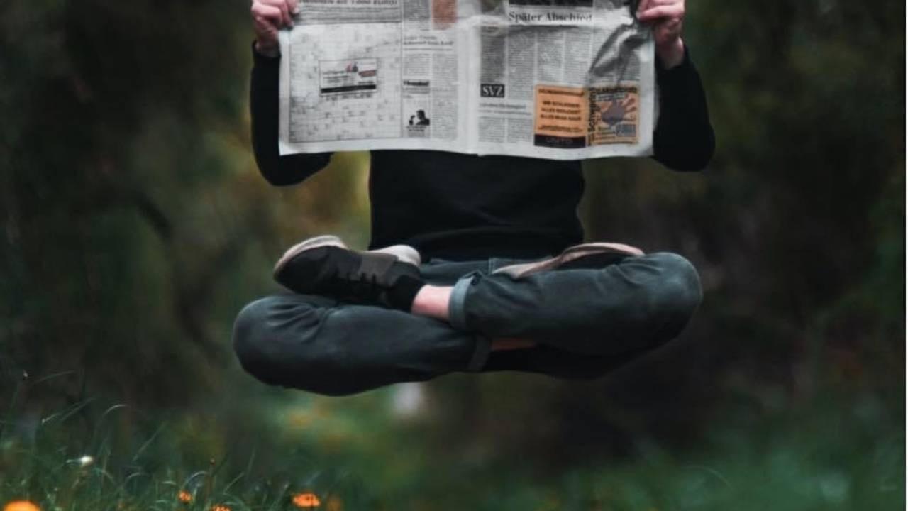 Persona che legge il giornale seduto perterra, con le gambe incrociate