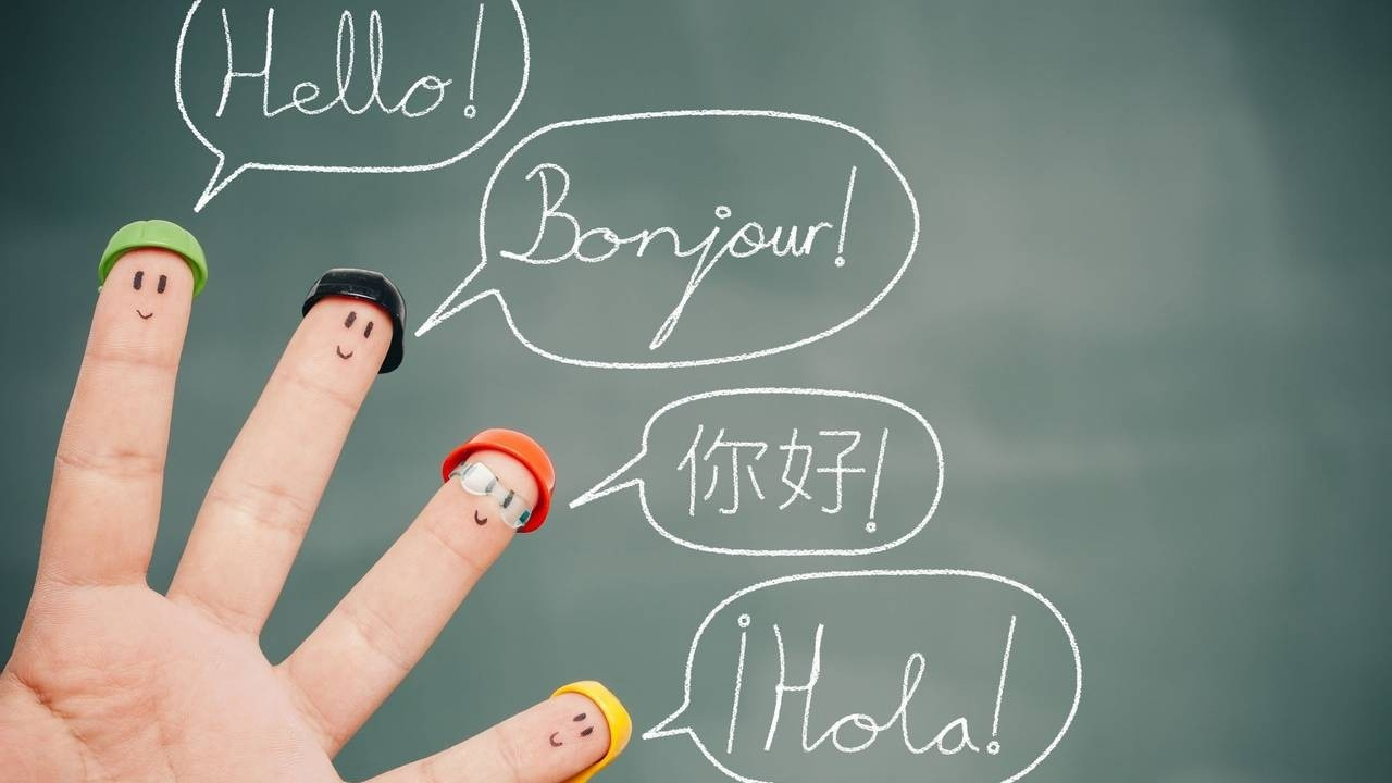 4 fingers with faces drawn on and wearing little hats. Speech bublbles drawn on a blackboard in the background say hello in different languages,