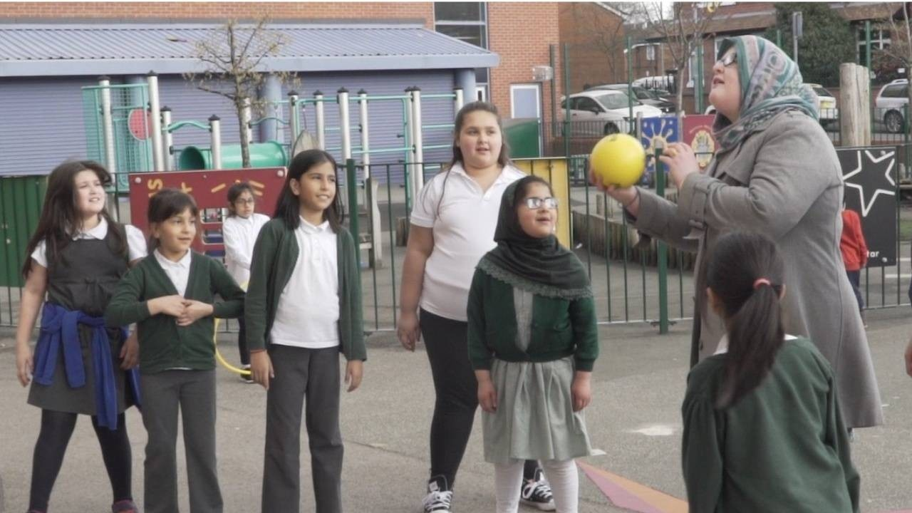 A mum is playing netball with five young girls in a primary school playground.
