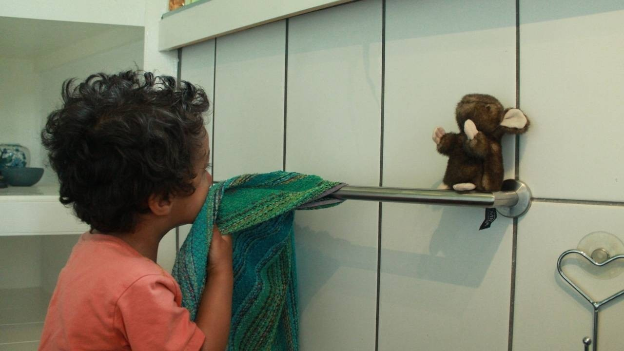 A boy drying his face near to  a toy mouse