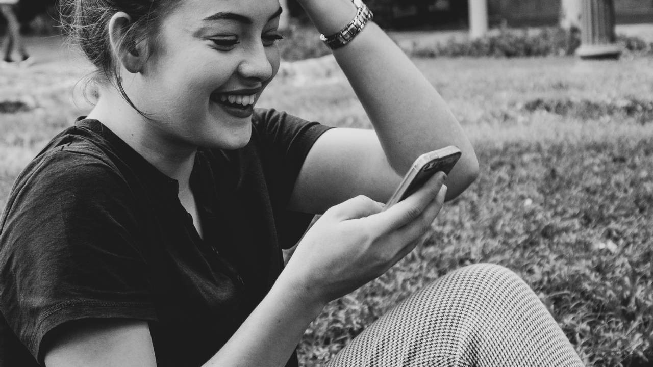 A happy young woman is looking at her phone.