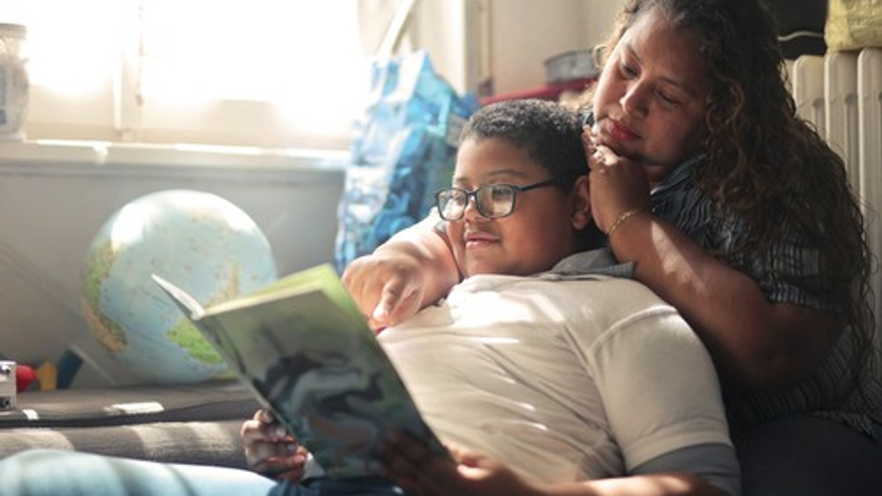 A mother and son read a book together.