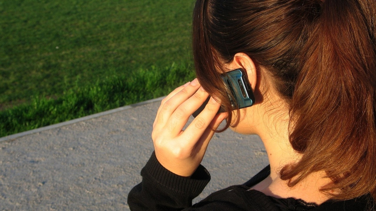 A women is on her phone, outdoors.