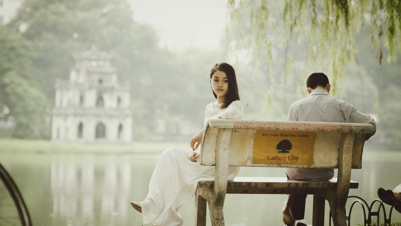 Unhappy woman sitting on a bench with her back facing a man