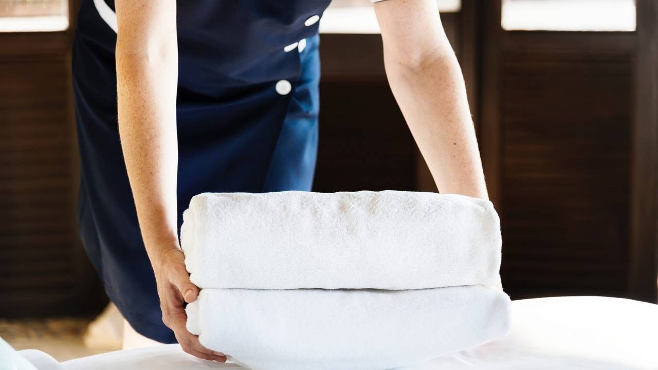 woman putting bath towels ls on the bed