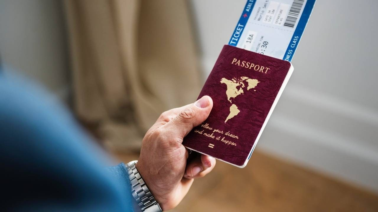 Adult holding a passport with a flight ticket