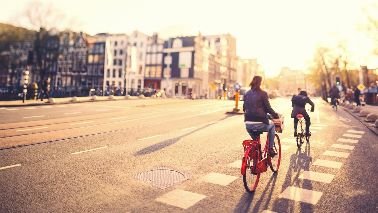 People on bikes in Amsterdam streets at sunset
