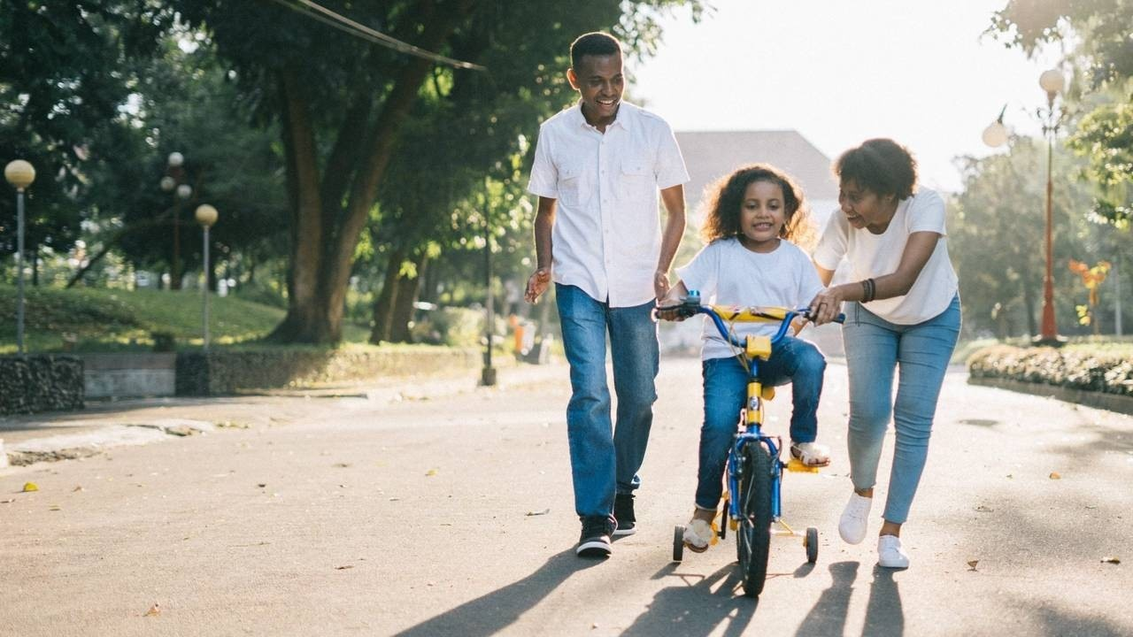 happy mom, dad and little girl cycling in the street