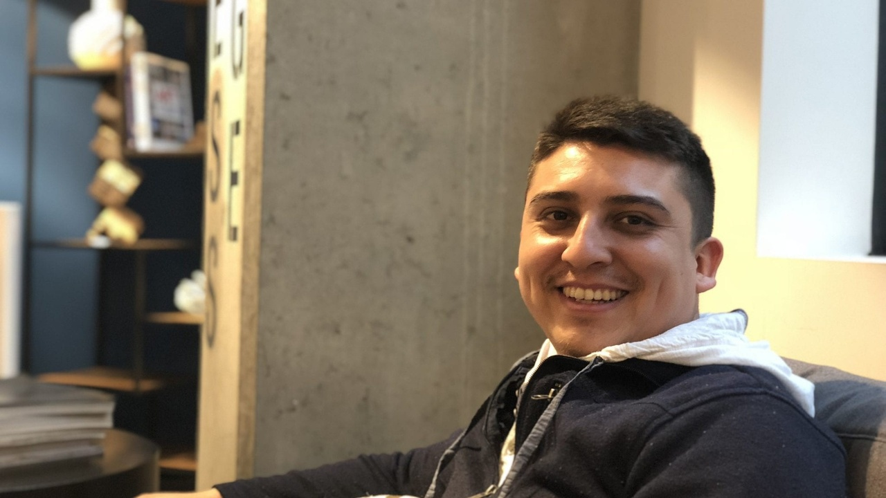 Young man sitting on couch smiling to camera