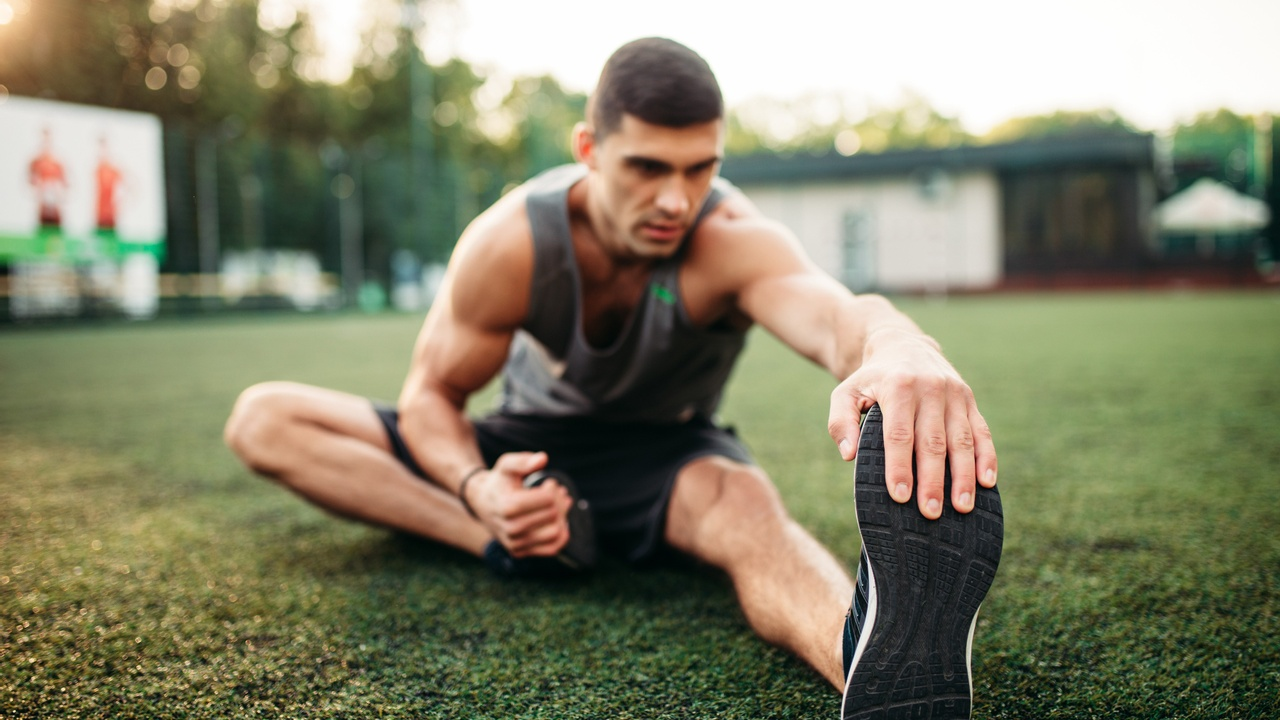 young male athlete stretching outside