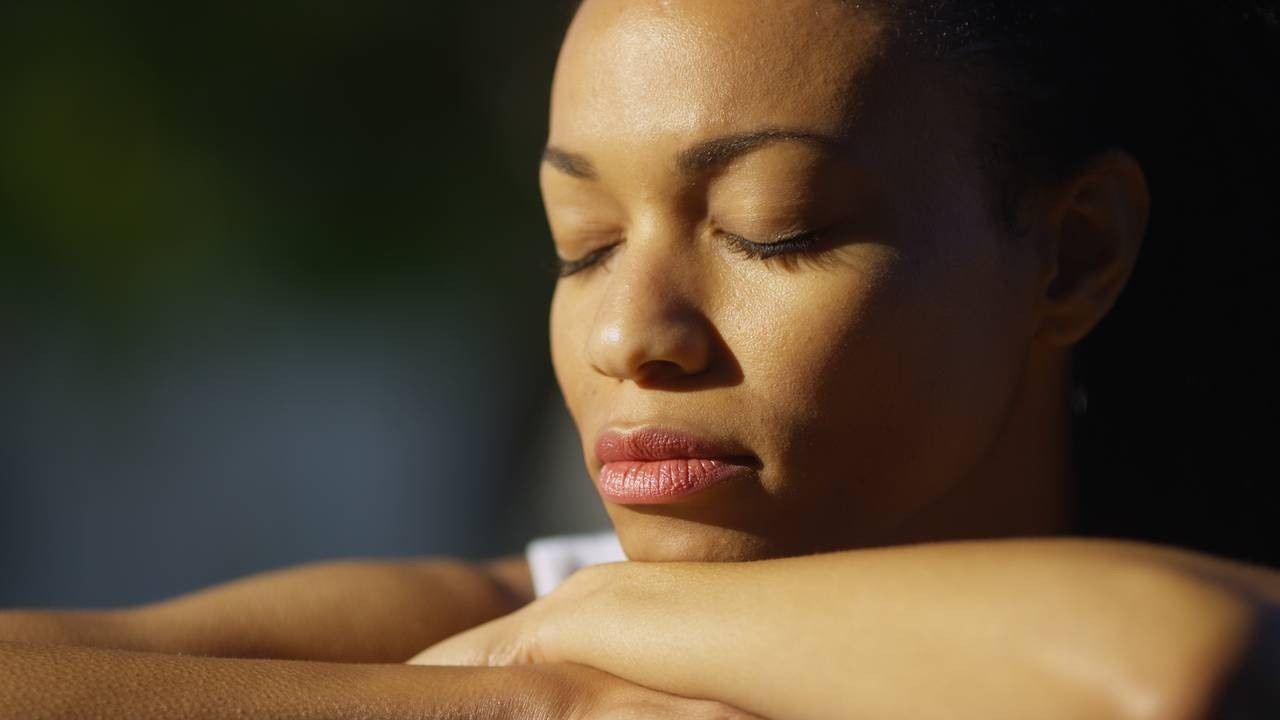 woman closing her eyes in the sunlight