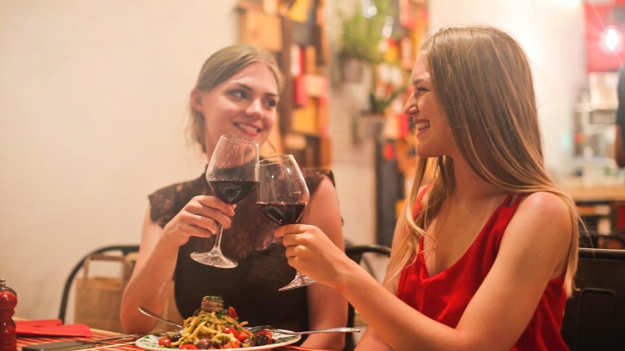twee dames drinken rode wijn tijdens een etentje
