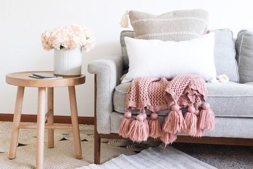picture of a living room couch with a soft pink throw over it