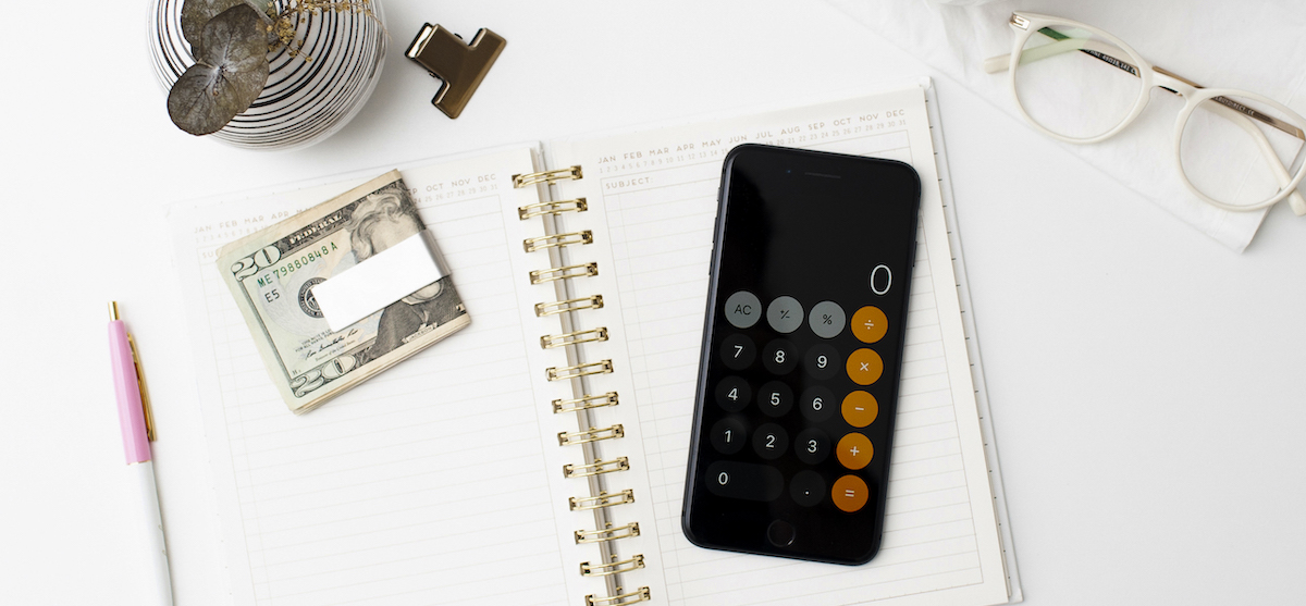 picture of a calculator and cash on top of a white journal