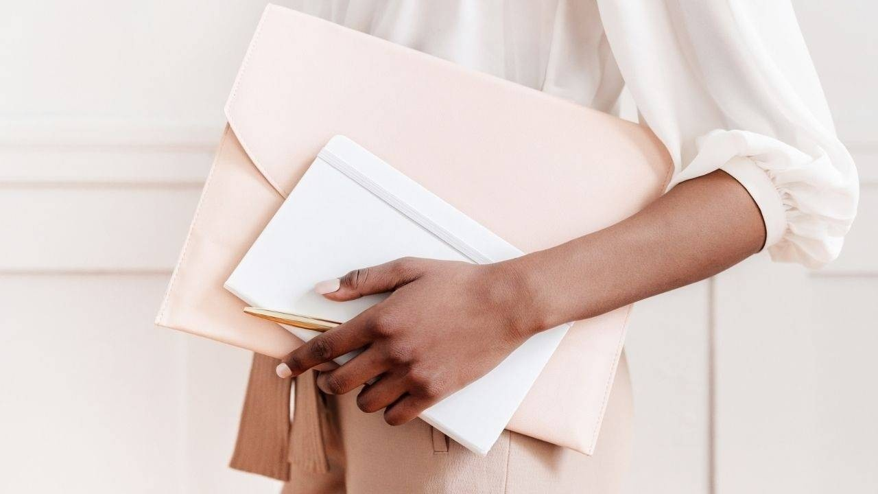 Airbnb property manager in blush colors holding an Airbnb management contract