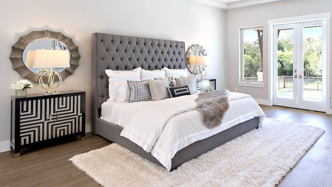 Staged primary bedroom with a gray upholstered bed with white bedding and black geometric patterned side tables