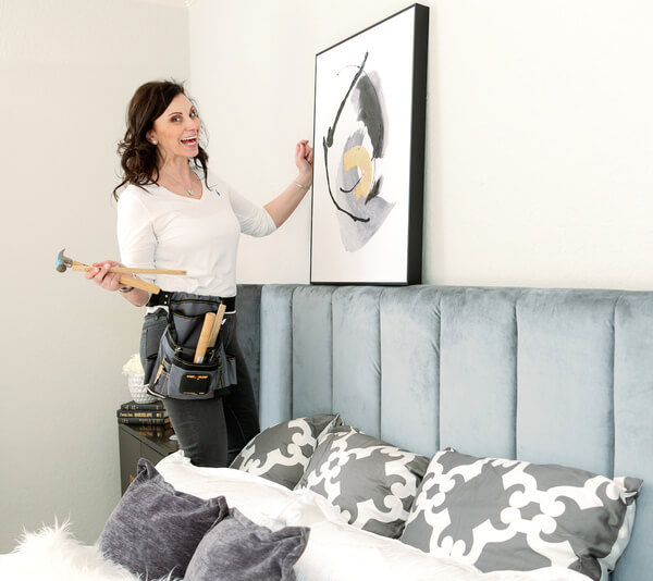 A woman hanging an art piece on her living room wall