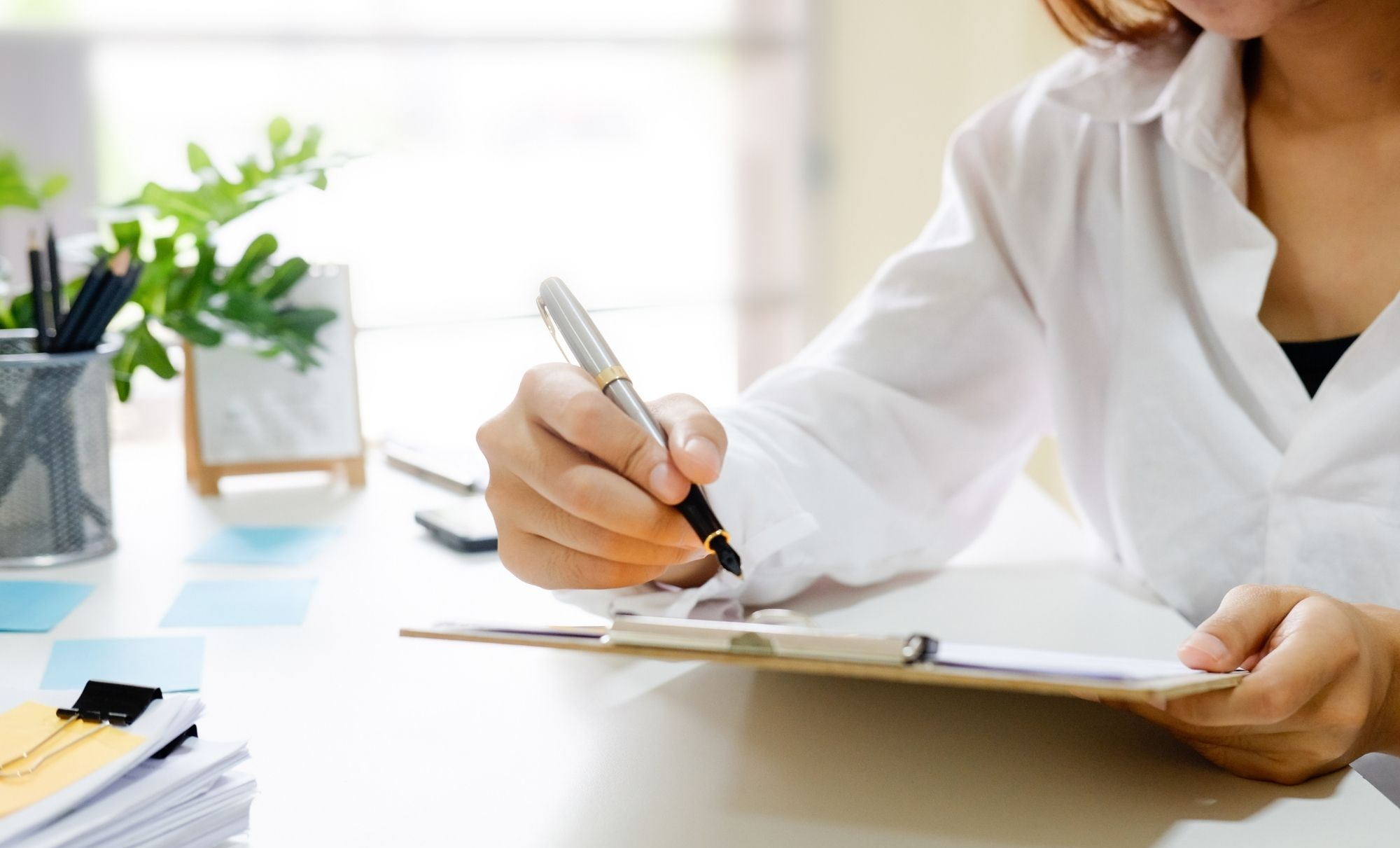 picture of a woman holding a pen and staging contract in a clipboard