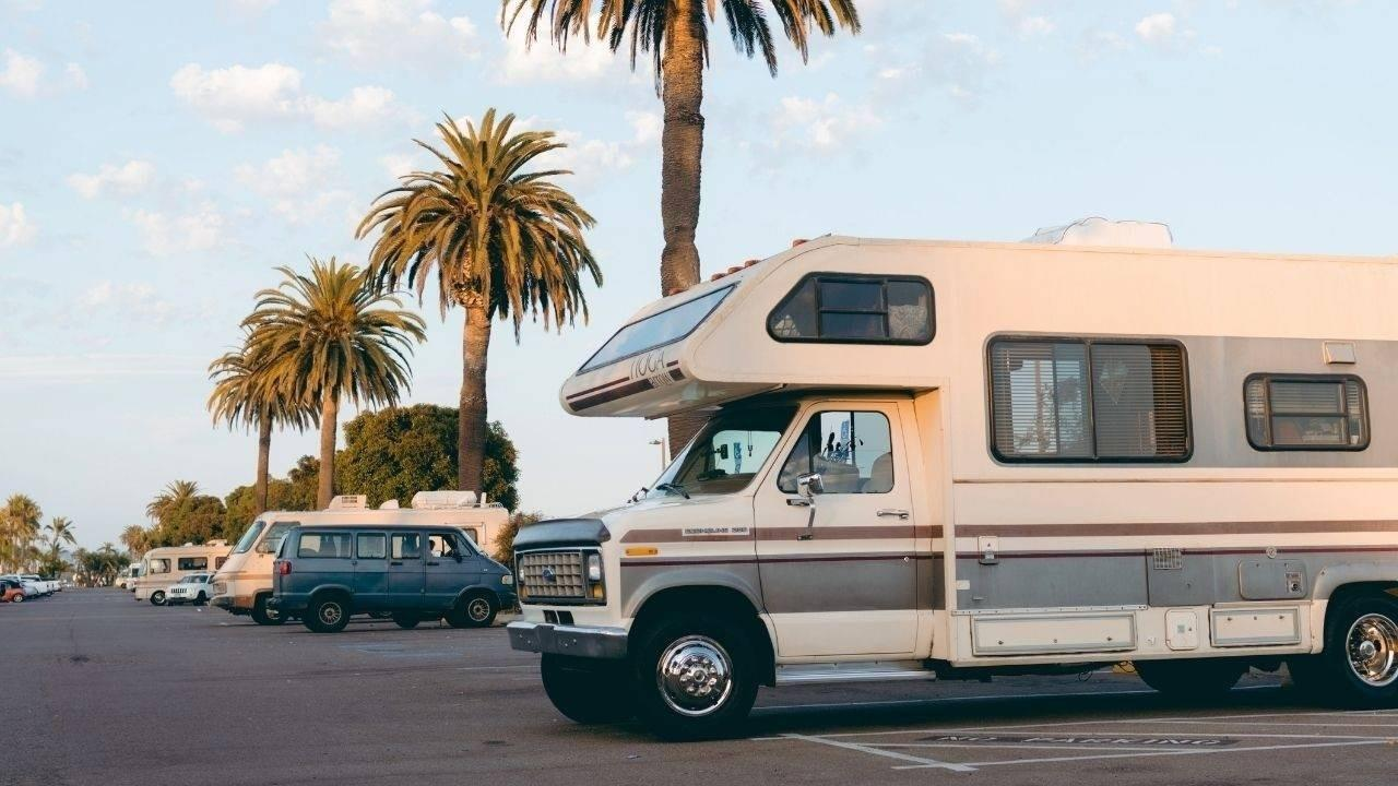 How to Create More Space in Your Airbnb: Lessons from the RV Industry. Words over an image of a camper RV parked in a parking lot with palm trees