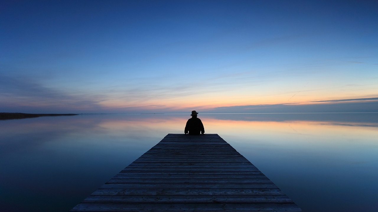 Person sitting on a jetty watching the sunset