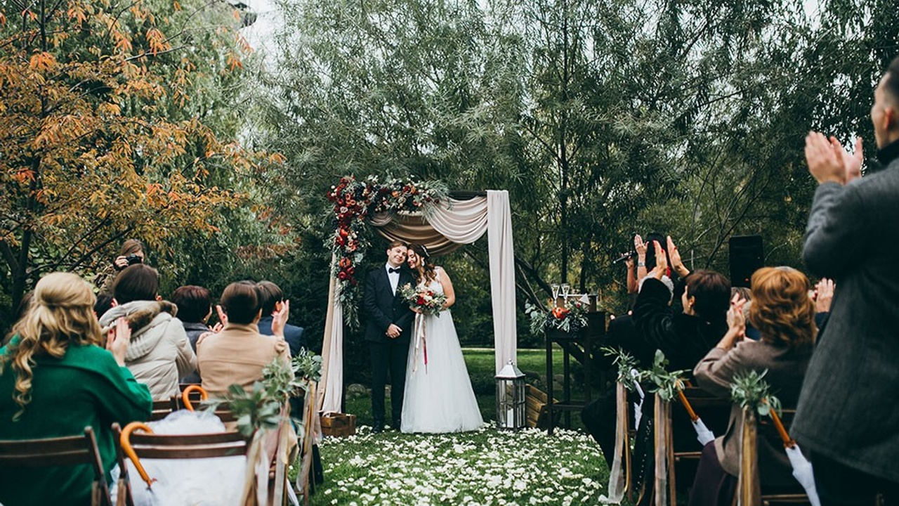 Couple stood outside in front of a wedding arch while their family celebrates