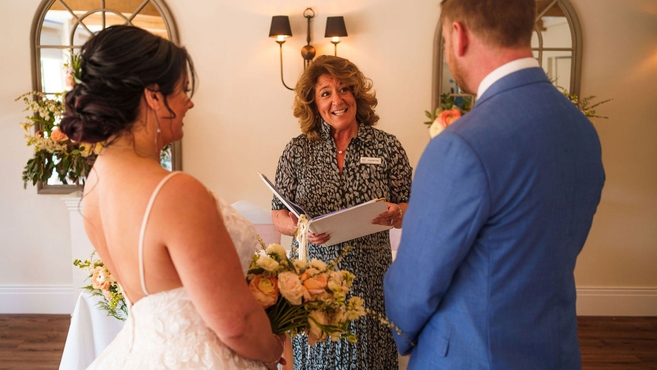 A bride and groom facing a celebrant, who is holding a folder and smiling.