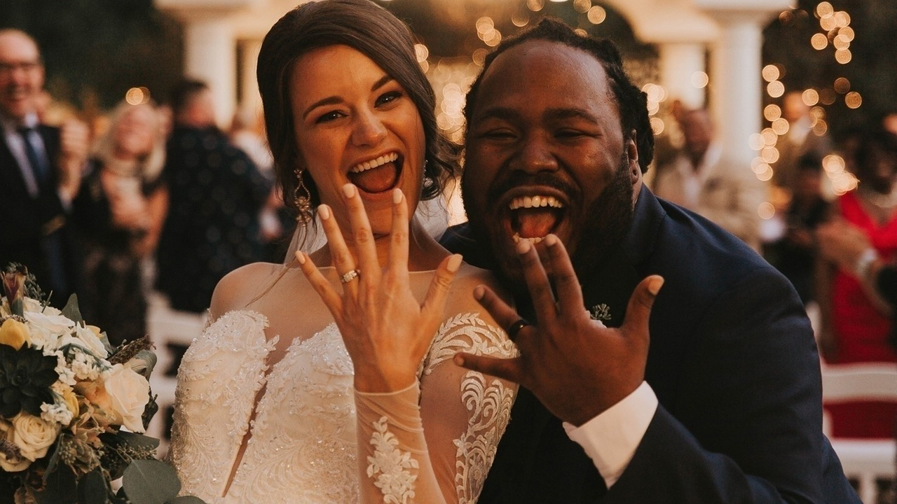 Married couple smiling showing off wedding rings