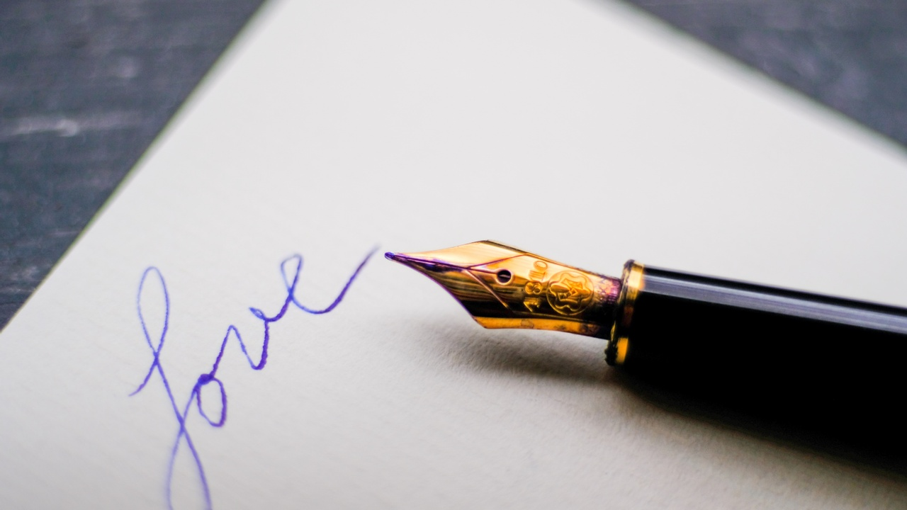 Paper with a black fountain pen laying on it. The word love is written in blue ink.