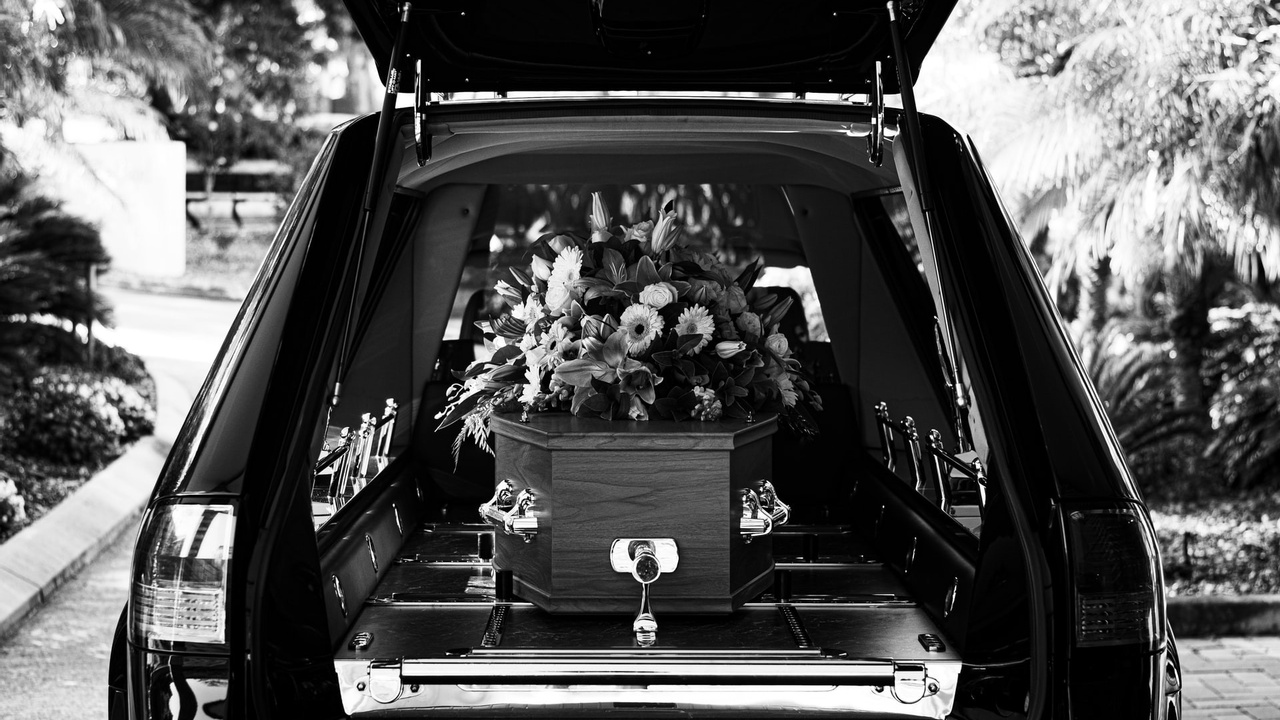 Black and white photo of a coffin in a hearse decorated with flowers