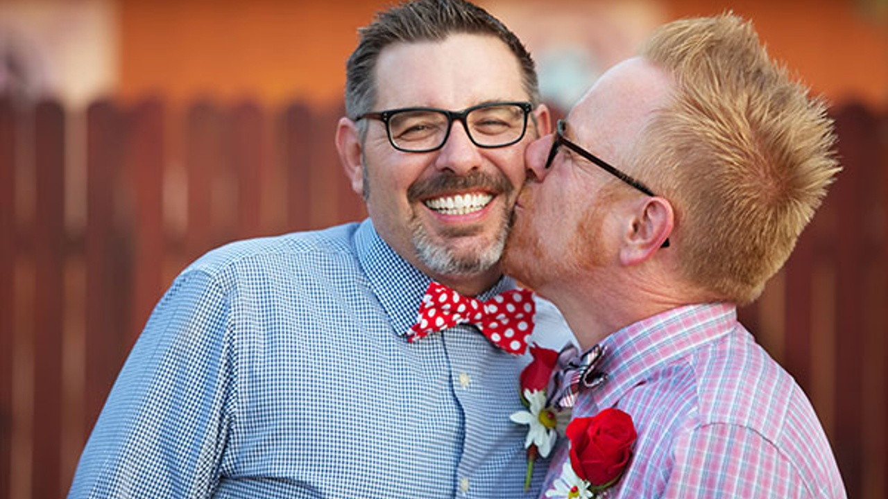 Two men, dressed smartly where bow ties. One is kissing the other on the cheek.