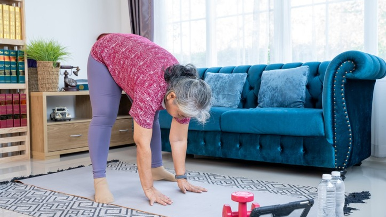 This woman is practicing Pilates online in her own home so she can be pain-free