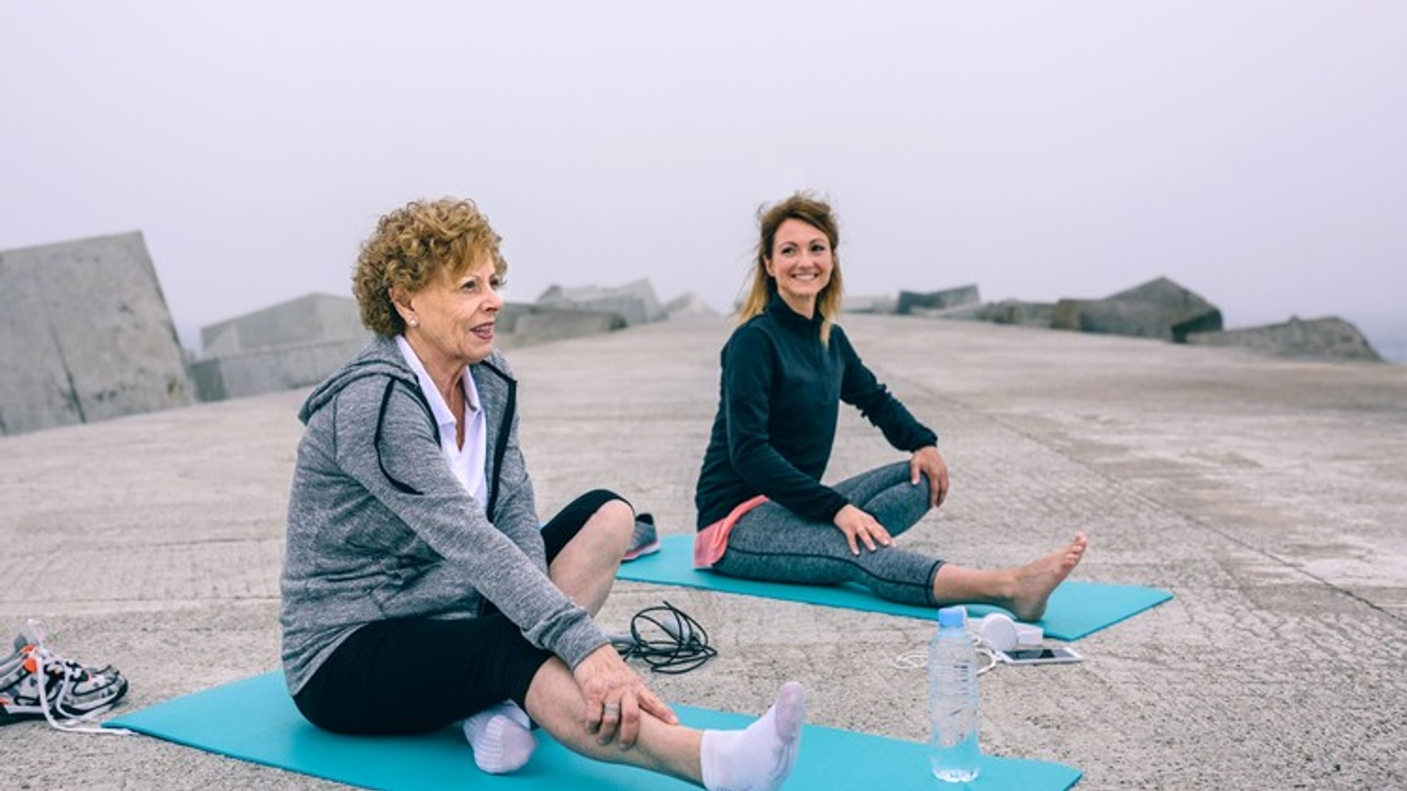 An older woman is doing Pilates with her teacher outside to prevent health issues as she ages