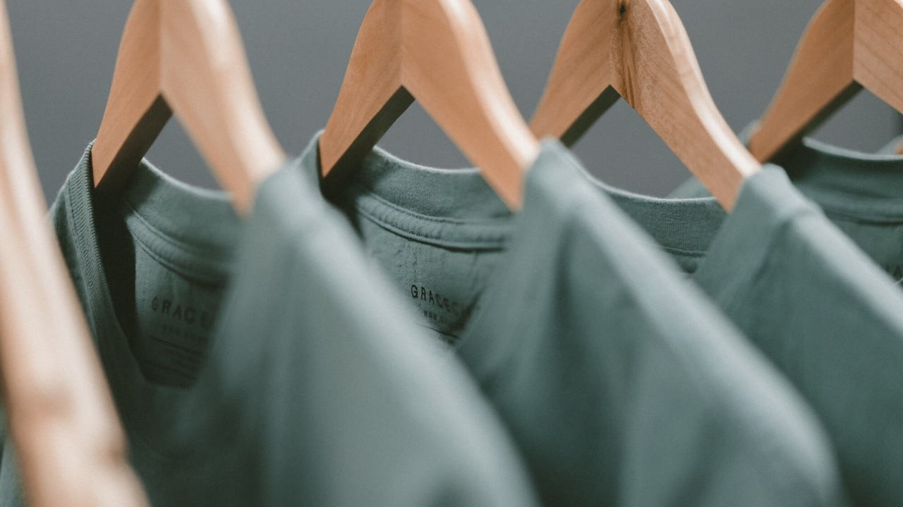 An image of grey/green t-shirts hanging on wooden coat-hangers to signify Sweatshops in Australia Exploit People With Disabilities
