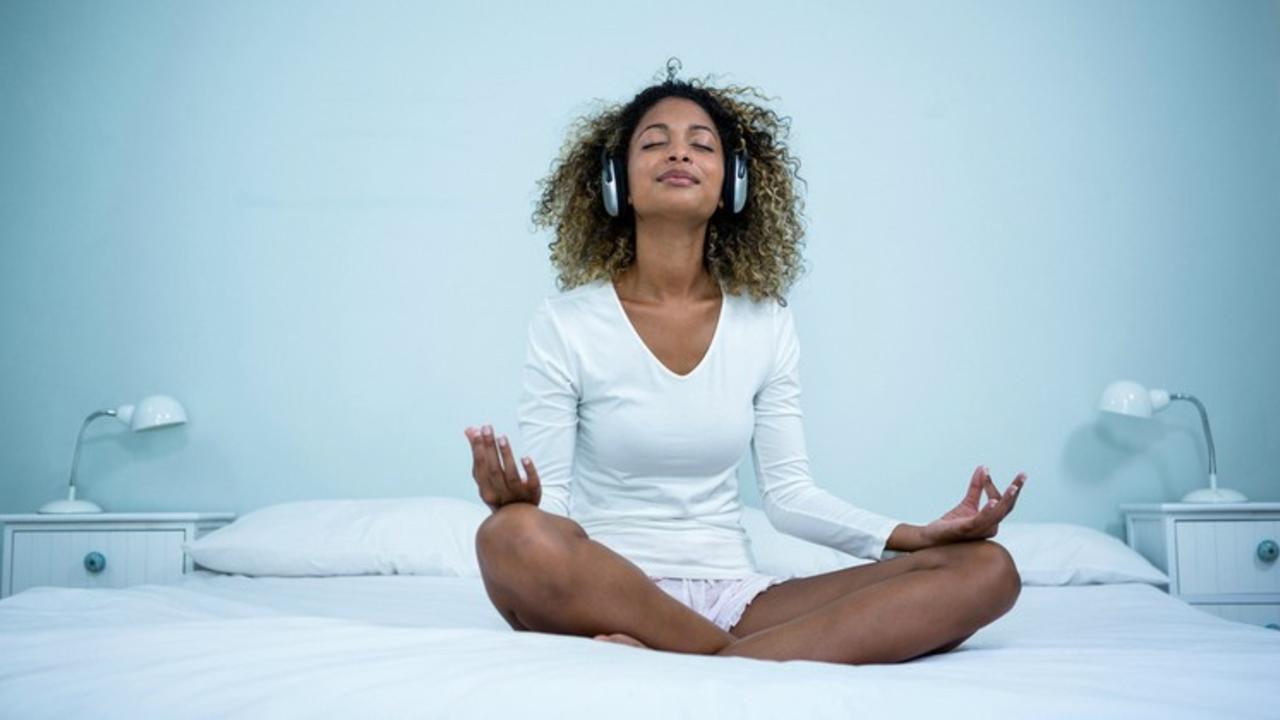 Iyi77pyltwl0tefod2kd woman meditating on bed with headphones