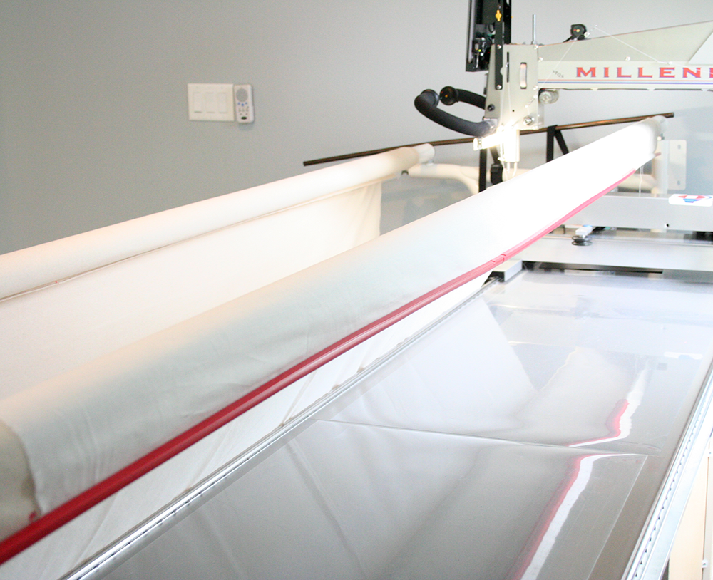 loading a quilt backing top edge secured with red snappers